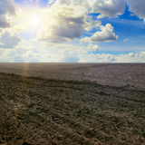 Plowed field and cloudy sky. Plowed field and sun on cloudy sky Stock Image