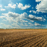 Plowed field and cloudy sky. In sunset Royalty Free Stock Image