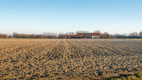 Plowed field and a farm Stock Images