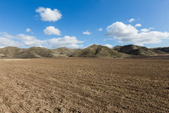 Plowed field and foothills Stock Photos