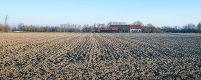 Plowed field in front of a farm Stock Image