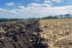 A plowed field after harvesting corn with a tractor complete with an eight-body plow against the sky and the landscape stock images