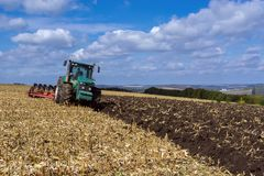 A plowed field after harvesting corn with a tractor complete wit stock photos