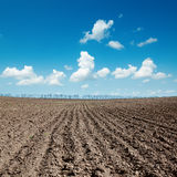 Plowed field after harvesting under blue sky Royalty Free Stock Photos