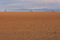 Plowed field and irrigation equipment royalty free stock image