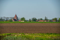 Plowed field and old village Royalty Free Stock Images