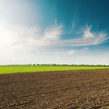 Plowed field in spring clouds in blue sky on sunset Royalty Free Stock Images