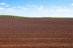 Plowed field in spring. And clouds over it Stock Photo