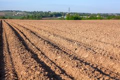 The plowed field at spring season, brown earth with seed furrows. The plowed field at spring season, brown earth with a seed furrows Royalty Free Stock Photography