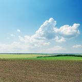 Plowed field in spring. Under cloudy sky Stock Photos