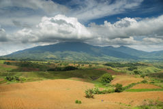Plowed field and tropical mountain Royalty Free Stock Photography