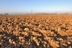 Plowed field under sun. Landscape of freshly plowed field in autumn sun Stock Photos