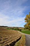 Plowed Field and Winding Road in Tuscany. Plowed field with a winding road through the Tuscan countryside royalty free stock image
