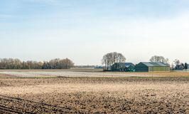 Plowed fields with a farm in the background. Dutch flat landscape with plowed fields in the foreground and a farm with barns in the background. It is early in Stock Photography