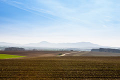 Plowed fields under blue sky. Sunny spring day with blue sky above the road between cultivated land with mountains in the background Stock Photos