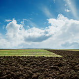 Plowed fields under cloudy sky. Green and plowed fields under cloudy sky Royalty Free Stock Images