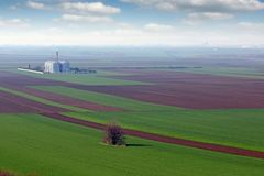 Plowed and green wheat fields and grain tank landscape Stock Image