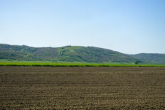 Plowed land by the hills Stock Image