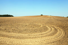 Plowed land, summer. Plowed land in the agricultural field after harvest of cereal, tractor tracks on the ground Royalty Free Stock Photo