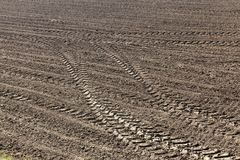 Plowed land with traces. Traces on the plowed land of the agricultural field during the preparation of the land for sowing, Photo close up Royalty Free Stock Photos
