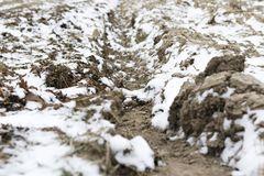 Plowed land in winter with deep furrows sprinkled with snow stock image
