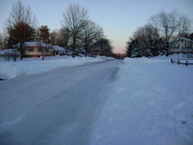 Plowed road in snowy suburb stock photos