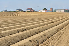 Plowed soil in the field and a village Royalty Free Stock Images