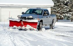 Plowing snow in a residential area. A  pick up with a plow moves snow after a storm in Michigan USA Stock Photo