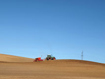 Plowing time. Red tractor working a wide field in Poland royalty free stock photography