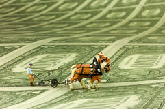 Plowman. Miniature figure of a plowman with two horses on a field of one dollar bills. With space for copy royalty free stock image