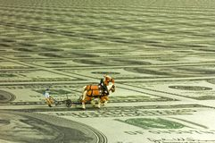 Plowman. Miniature figure of a ploughman with two horses on a field of one hundred dollar bills. With space for copy stock images