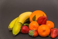 plátano, manzana, naranja, fresas y mandarina tres con las hojas en un fondo gris hermoso, colores hermosos y compositi Imagen de archivo libre de regalías