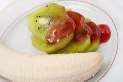Plátano y kiwi cortado y rematado con el jarabe de fresa Foto de archivo libre de regalías