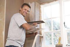 Plâtrier travaillant au mur intérieur Photographie stock libre de droits