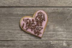 Plätzchen bedeckt mit rosa Zuckerglasur und Schokoladensplittern Stockfoto