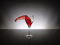 Pluśnięcia czerwone wino na szkle Zdjęcia Royalty Free