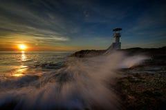 Pluśnięcie fala przy latarnią morską Obrazy Stock