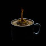Pluśnięcie kawa i mleko w białej filiżance Zdjęcie Stock