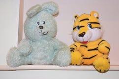 Pluchespeelgoed: een Blauwachtig Konijntje met lange oren en een gele tijger werpen met een zwarte streep stock afbeeldingen