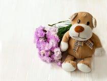 Pluchestuk speelgoed puppy met een boeket Stock Foto