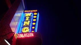 Pluckers Wing Bar Sign på natten Royaltyfri Bild