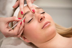 Plucking eyebrows with tweezer by beautician in beauty salon. Stock Photo