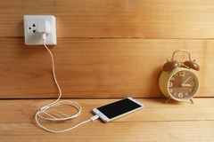 Plug in Adapter power cord charger of laptop computer On wooden floor. With sun Warm light royalty free stock photo
