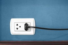 Plug on blue wall Royalty Free Stock Photo