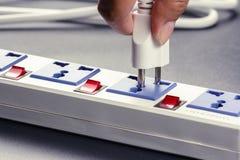 Plug in. Closeup hand insert plug into multiple socket bar royalty free stock photography
