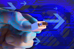 Plug into the future. Composite of a Hand holding a cord and plug with a circuit board and arrows Royalty Free Stock Photography