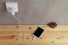 Plug in power outlet Adapter cord charger of mobile phone on wooden royalty free stock images