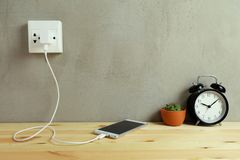 Plug in power outlet Adapter cord charger of mobile phone on wooden stock photo