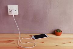 Plug in power outlet Adapter cord charger of mobile phone on wooden royalty free stock image