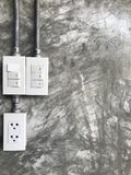 Plug the power outlet and the power switch on the cement wall. Plug the power outlet and the power switch on the grey cement wall stock photos